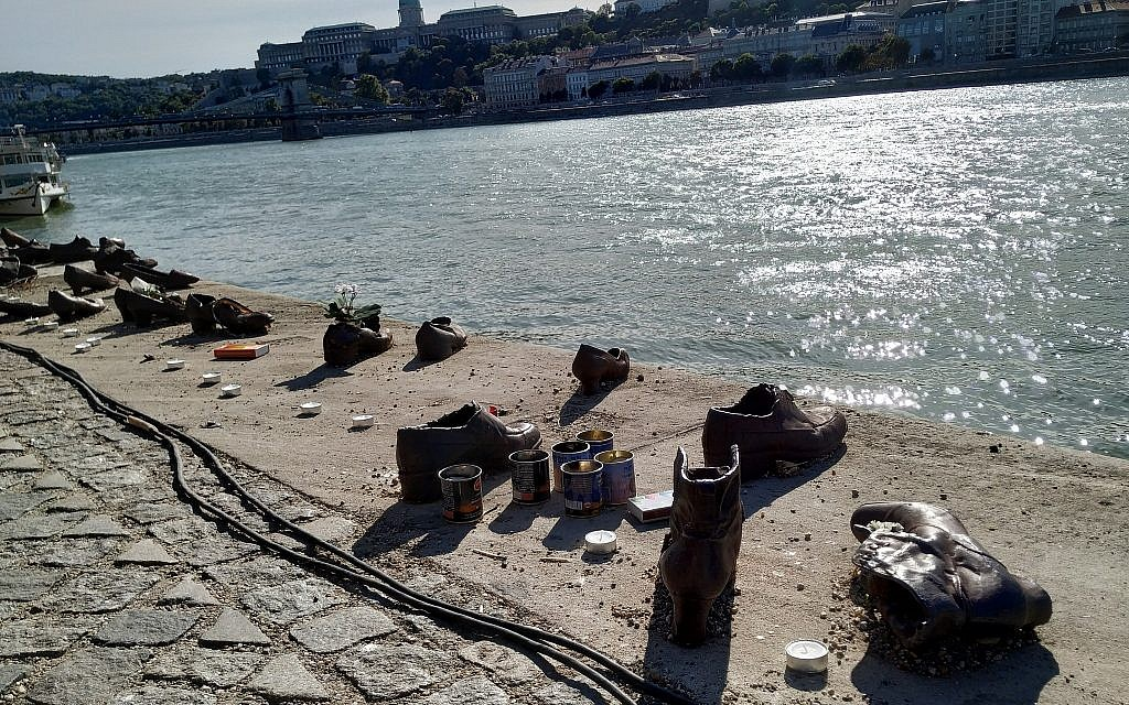 Memorial candles dot the bronzed shoe memorial to Holocaust victims shot on the bank of the Danube River in Budapest, September 22, 2019. (Yaakov Schwartz/ Times of Israel)