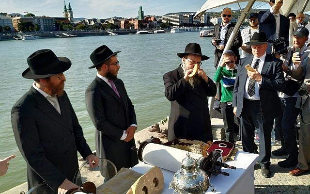 Rabbi Baruch Oberlander, right, blows the shofar horn on the bank of the Danube River at a ceremony dedicating two new synagogues and two new Torah scrolls in Budapest, September 22, 2019. (Yaakov Schwartz/ Times of Israel)
