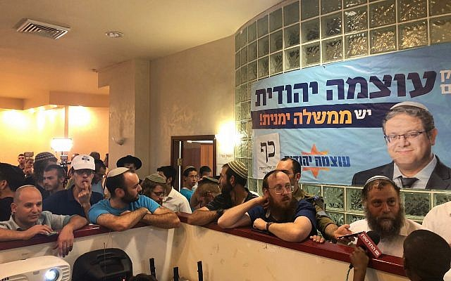 Otzma Yehudit supporters watch the exit poll results at the campaign headquarters in Jerusalem on September 17, 2019. (Jacob Magid/Times of Israel)