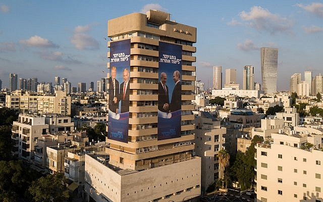Election campaign posters on the Likud party headquarters building in Tel Aviv showing Prime Minister Benjamin Netanyahu shaking hands with Russian President Vladimir Putin and US President Donald Trump, July 28, 2019. (Adam Shouldman/Flash90)