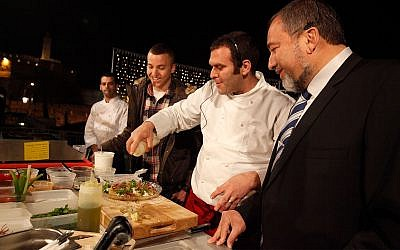 Avigdor Liberman and his son Amos cook with a chef at a food festival held in Jerusalem, March 29, 2011. (Miriam Alster/Flash90)