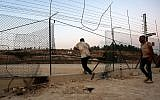 Illustrative: Palestinians illegally cross the border fence into Israel on the outskirts of the West Bank city of Hebron, August 6, 2019. (Wisam Hashlamoun/Flash90)