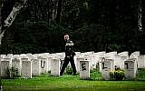 A police officer walks past graves which have been vandalized with graffiti in the British World War II Commonwealth Graves cemetery in Mierlo, east of Eindhoven, Netherlands, September 13, 2019. (Rob Engelaar/ANP/AFP)