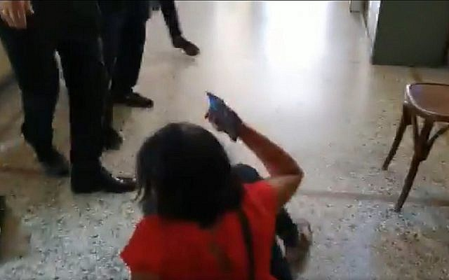 Screen capture from video showing Kan public broadcaster reporter Vered Pelman, bottom, after having been allegedly shoved to the floor by family members of one of two Israeli rape suspects in Greece, September 3, 2019. (Twitter)