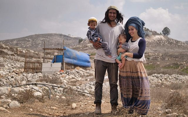 Neria Zarog (c) with his wife and child in front of their home in the Kumi Ori outpost, a neighborhood of the Yitzhar settlement in the northern West Bank. The IDF has issued an order barring him from the West Bank. (Avraham Shapira)