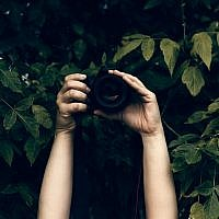 A creep taking pictures from behind bushes. (MarinaZg/Istock by Getty Images)
