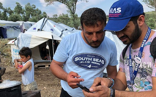 HIAS Greece translator Jalal Barezkai (R) works with a Syrian refugee in an encampment just outside the Moria refugee camp on the Greek island of Lesvos, May 9, 2018. Barezkai is a former refugee from Afghanistan. (Bill Swersey/HIAS via JTA)