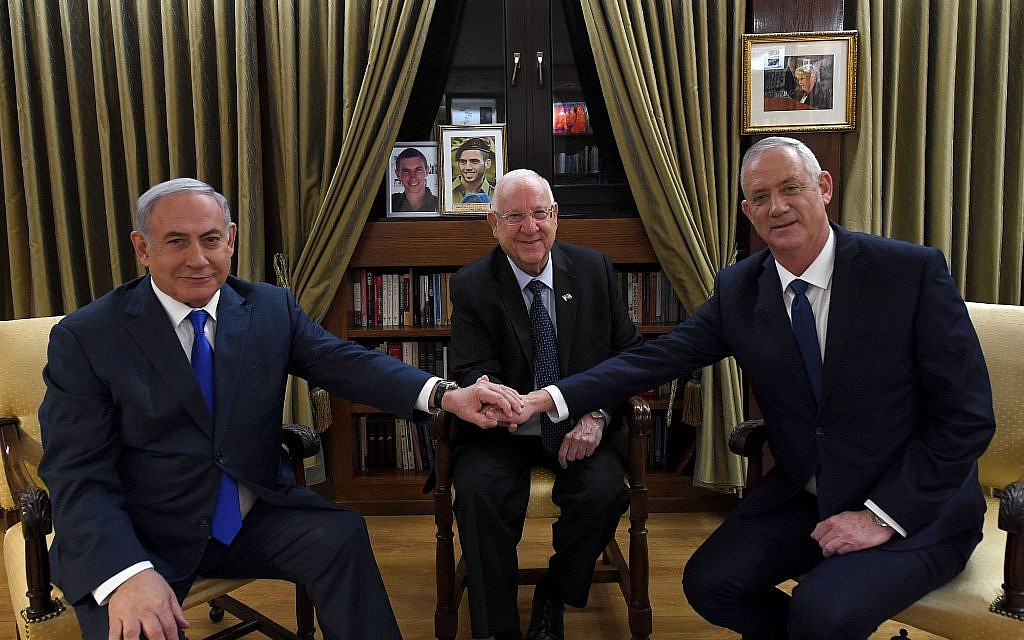 Prime Minister Benjamin Netanyahu (L) shakes hands with Blue and White party leader Benny Gantz (R) as President Reuven Rivlin looks on, at the President's Residence in Jerusalem, on September 23, 2019. (Haim Zach/GPO)