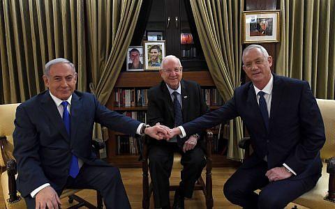 Prime Minister Benjamin Netanyahu (L) shakes hands with Blue and White party leader Benny Gantz (R) as President Reuven Rivlin looks on, at the President's Residence in Jerusalem, on September 23, 2019. (Haim Zach/GPO)