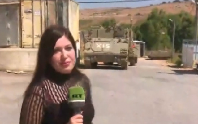 A reporter for the Russian television network RT in Arabic wondering around an empty IDF outpost on the Lebanese border near Avivim, a day after it was struck by Hezbollah missiles. (RT screenshot via Channel 12)