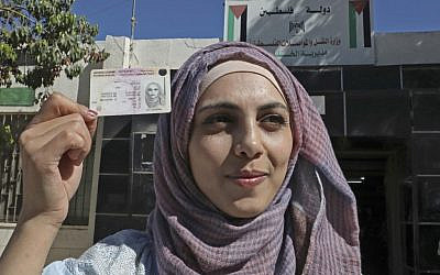 Palestinian Dalia al-Darawish holds her truck driver's license after passing her driving test, in the West Bank town of Hebron on September 25, 2019  (HAZEM BADER / AFP)