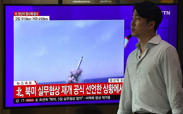A man walks past a television news screen showing file footage of a North Korean missile launch, at a railway station in Seoul on October 2, 2019. (Jung Yeon-je / AFP)