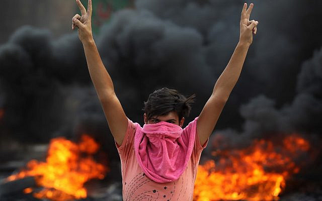 An Iraqi protester flashes the v-sign during a demonstration against state corruption, failing public services and unemployment in the Baladiyat district of the capital Baghdad on October 2, 2019 (AHMAD AL-RUBAYE / AFP)