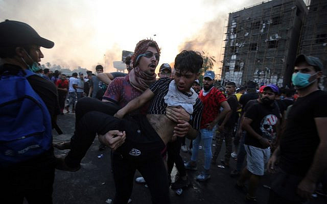 An Iraqi protester carries a wounded comrade during a demonstration against state corruption, failing public services and unemployment at Tayaran square in Baghdad on October 2, 2019. (AHMAD AL-RUBAYE/AFP)