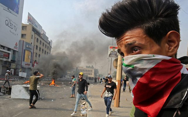 A protester wearing an Iraqi national flag as a bandana face mask stands during clashes between protesters and riot police amidst demonstrations against state corruption, failing public services, and unemployment, in the Iraqi capital Baghdad's central Tahrir Square on October 3, 2019. (AHMAD AL-RUBAYE/AFP)
