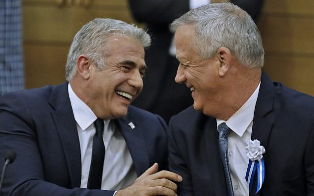 Blue and White leaders Benny Gantz, right, and Yair Lapid, left, share a laugh during a faction meeting at the Knesset on October 3, 2019. (Menahem Kahana/AFP)