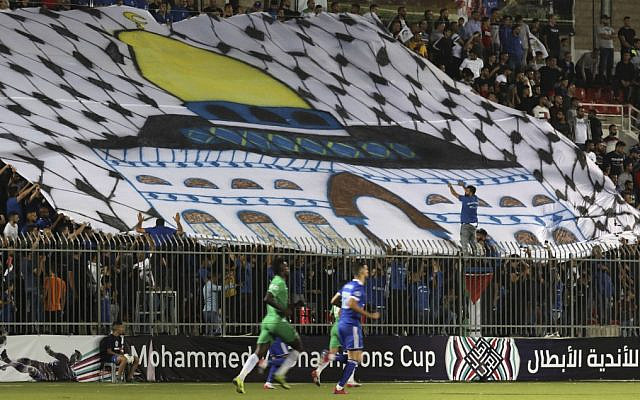 Spectators hold a huge flag depicting Jerusalem's Dome of the Rock shrine during a match between Palestinian team Hilal al-Quds and Morocco's Raja Casablanca in the Arab Champions Cup at Faisal Husseini stadium in the town of al-Ram, between Jerusalem and Ramallah, on October 3, 2019. (ABBAS MOMANI / AFP)