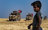 A Syrian boy watches as Turkish military vehicles, part of a US military convoy, take part in a joint patrol in the Syrian village of al-Hashisha on the outskirts of Tal Abyad along the border with Turkey, on October 4, 2019. (Delil Souleiman/AFP)