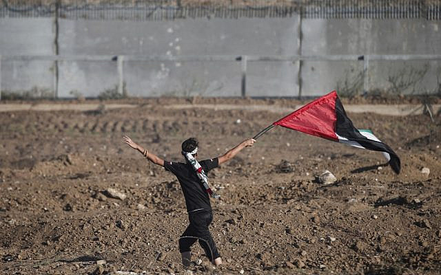 A young protester waves a Palestinian flag while demonstrating by the border fence with Israel east of Gaza City on October 4, 2019. (MAHMUD HAMS / AFP)