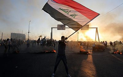 An Iraqi protester waves the national flag during a demonstration against state corruption, failing public services, and unemployment, in the Iraqi capital Baghdad on October 5, 2019. (AHMAD AL-RUBAYE/AFP)