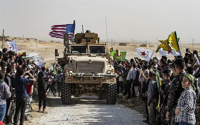 Syrian Kurds gather around a US armored vehicle during a demonstration against Turkish threats, next to a US-led international coalition base on the outskirts of Ras al-Ain town in Syria's Hasakeh province near the Turkish border, on October 6, 2019. (Delil Souleiman/AFP)