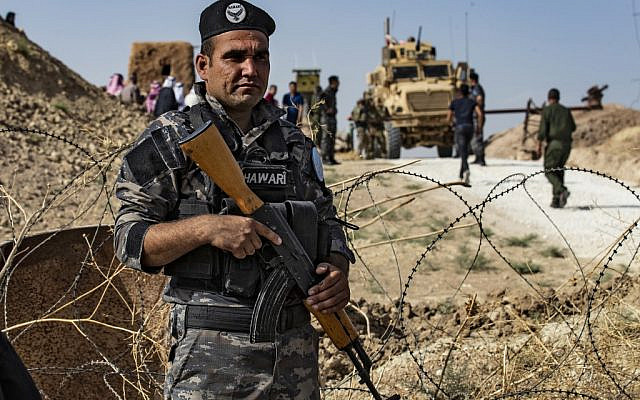 A member of Kurdish security forces stands guard during a demonstration by Syrian Kurds against Turkish threats next to a base for the US-led international coalition on the outskirts of Ras al-Ain town in Syria's Hasakeh province near the Turkish border on October 6, 2019. (Delil SOULEIMAN / AFP)