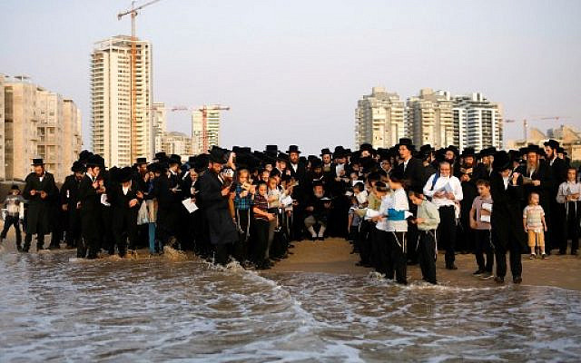"Ultra-Orthodox Jewish men surround their rabbi as they pray on a beach in the southern Israeli town of Ashdod, while performing the ""Tashlich"" ritual on October 7, 2019 ahead of Yom Kippur. ( MENAHEM KAHANA / AFP)"