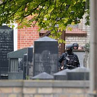 Policemen are seen behind gravestones of a Jewish cemetery close to the site of a shooting in Halle an der Saale, eastern Germany, on October 9, 2019 (Sebastian Willnow / dpa / AFP) / Germany OUT