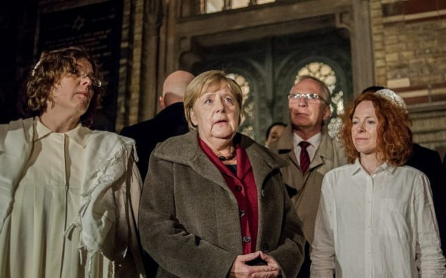 German Chancellor Angela Merkel (C) talks to Rabbi Gesa Ederberg (L) and other members of the Jewish community at a vigil outside the New Synagogue in Berlin on October 9, 2019. (Anton Roland LAUB/AFP)