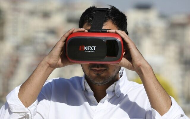 Salem Barameh, executive director of the Palestine Institute for Public Diplomacy, uses a headset for the 'Palestine VR' tour guide application, on October 10, 2019, in the West Bank city of Ramallah. (Abbas Momani/AFP)