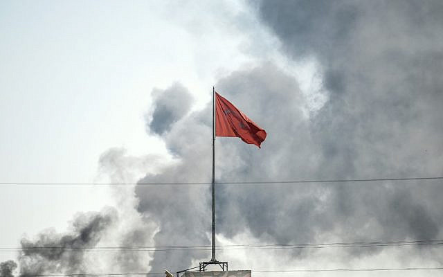 A picture taken in Akcakale at the Turkish border with Syria on October 10, 2019 shows the Turkish flag as smokes rises from the Syrian town of Tal Abyad after a mortar landed in Akcakale. (BULENT KILIC / AFP)