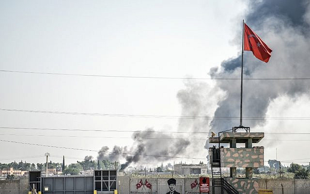 A picture taken in Akcakale at the Turkish border with Syria shows smokes rising from the Syrian town of Tal Abyad after a mortar fired from Syria landed in the garden of a Turkish government building in Akcakale. (BULENT KILIC / AFP)