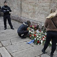 People place flowers at a makeshift memorial in front of the synagogue in Halle, eastern Germany, on October 10, 2019, one day after the attack where two people were shot dead. (AXEL SCHMIDT / AFP)