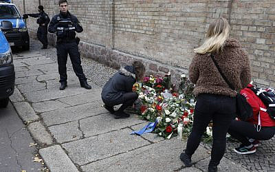 People place flowers at a makeshift memorial in front of the synagogue in Halle, eastern Germany, on October 10, 2019, one day after the attack where two people were shot dead. (Axel Schmidt/AFP)