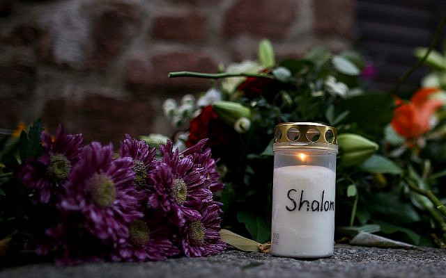 Candles and flowers are seen at a makeshift memorial in front of the synagogue in Halle, eastern Germany, on October 10, 2019, one day after the attack where two people were shot dead in an anti-Semitic attack. (Ronny Hartmann/AFP)