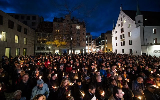 Mourners hold candles as they attend a vigil in commemoration of the Halle shooting victims in front of the Ohel Jakob synagogue in Munich, southern Germany, on October 10, 2019, one day after the deadly anti-Semitic shooting in Halle. (Matthias Balk/DPA/AFP)