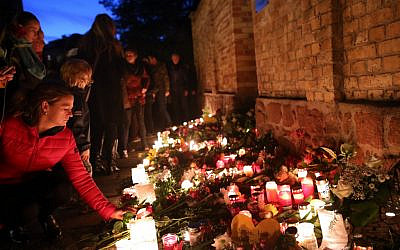Mourners light candles on October 10, 2019, at the synagogue in Halle, eastern Germany, one day after a deadly anti-Semitic shooting. (Ronny Hartmann/AFP)