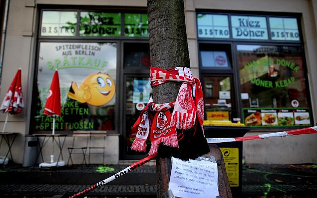 Scarves of German soccer clubs Hallescher FC and Rot-Weiss Erfurt are seen wrapped around a tree on October 10, 2019, outside the doner kebab restaurant in Halle, eastern Germany, that was one of the sites of an anti-Semitic shooting in which two people were killed. (Ronny Hartmann/AFP)