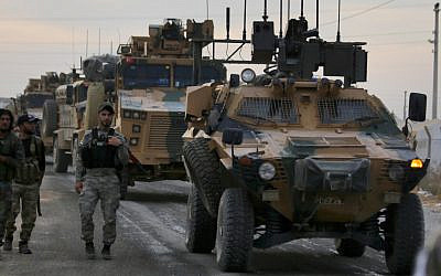 Turkish-backed Syrian fighters walk next to Turkish army vehicles near the village of Akcakale along the border with Syria on October 11, 2019, as they prepare to take part in the Turkish-led assault on northeastern Syria. (Bakr Alkasem/AFP)