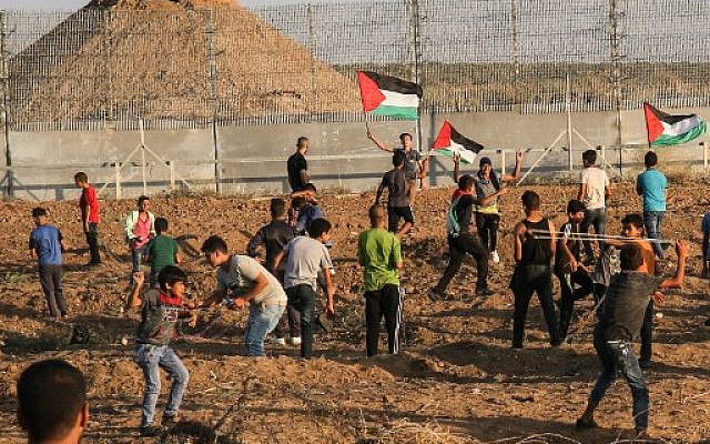 Palestinians riot by the border fence between the Gaza Strip and Israel, east of Gaza City, on October 11, 2019. (Said Khatib/AFP)