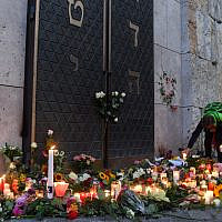 Two women light candles among others and flowers next to the entrance of the synagogue in Munich, during a protest against anti-Semitism on October 11, 2019 two days after a deadly shooting outside a synagogue in Halle. (Photo by Christof STACHE / AFP)