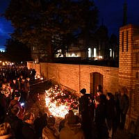 Mourners stand around a makeshift memorial of candles and flowers at the synagogue in Halle an der Saale, eastern Germany, on October 11, 2019, two days after a deadly shooting. - The German suspect in the attack targeting the synagogue has admitted to the shooting rampage and confessed that it was motivated by anti-Semitism and right-wing extremism, federal prosecutors said. (Photo by Hendrik Schmidt / dpa / AFP) / Germany OUT