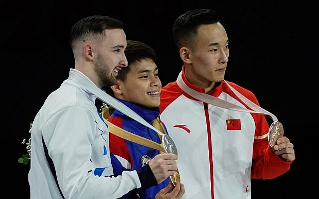 (L-R) 2nd placed Israel's Artem Dolgopyat, winner Philippines' Carlos Edriel Yulo and 3rd placed China's Xiao Ruoteng pose on the podium during the medal ceremony for the Men's floor event at the FIG Artistic Gymnastics World Championships at the Hanns-Martin-Schleyer-Halle in Stuttgart, southern Germany, on October 12, 2019. (Lionel BONAVENTURE / AFP)
