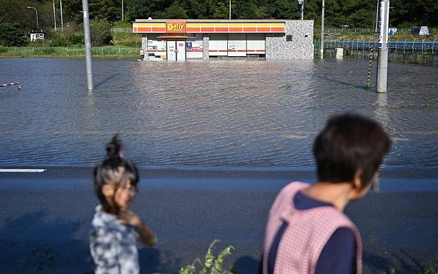 People walk by a flooded convenience store in the aftermath of Typhoon Hagibis in Kakuda, Miyagi Prefecture on October 13, 2019. (CHARLY TRIBALLEAU / AFP)