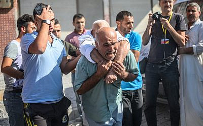 An elderly man is evacuated from a building in Akcakale, a town near the Turkish border with Syria, on October 13, 2019, after it was hit by a rocket reported to be fired from within Syria. (Photo by BULENT KILIC / AFP)