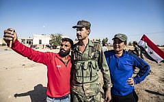 Locals welcome Syrian regime forces as they arrive at the western entrance of the town of Tal Tamr, in the countryside of Syria's northeastern Hasakeh province, on October 14, 2019. (Delil Souleiman/AFP)