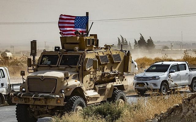 In this file photo taken on October 6, 2019, a US soldier sits atop an armored vehicle during a demonstration by Syrian Kurds against Turkish threats next to a base for the US-led international coalition on the outskirts of Ras al-Ain town in Syria's Hasakeh province near the Turkish border (AFP)