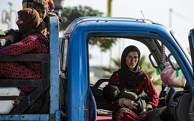 Syrian families fleeing the battle zone between Turkey-led forces and Kurdish fighters from the Syrian Democratic Forces (SDF) in and around the northern flashpoint town of Ras al-Ain on  the border with Turkey, arrive along with Syrian Arab and Kurdish civilians in the city of Tal Tamr on the outskirts of Hasakeh on October 15, 2019.  ( Delil SOULEIMAN / AFP)