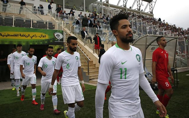 The Saudi and Palestinian national football teams enter the pitch during a World Cup 2022 Asian qualifying match between Palestine and Saudi Arabia in the town of al-Ram in the West Bank on October 15, 2019. (HAZEM BADER / AFP)