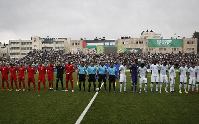 The Saudi and Palestinian national football teams listen to their national anthems during a World Cup 2022 Asian qualifying match between Palestine and Saudi Arabia in the town of al-Ram in the West Bank on October 15, 2019. (HAZEM BADER/AFP)